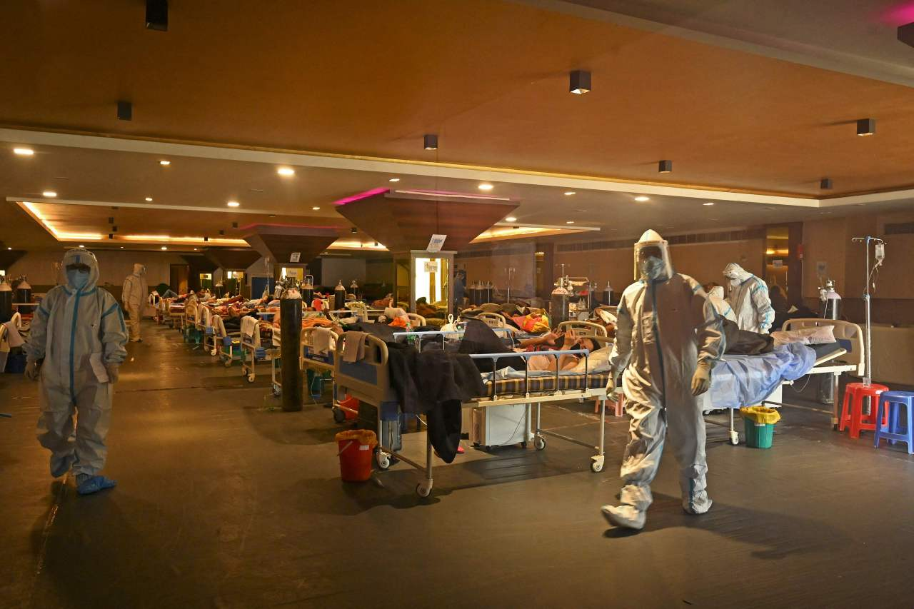 Health workers wearing personal protective equipment (PPE kit) attends to COVID-19 coronavirus positive patients inside a banquet hall temporarily converted into a covid care centre in New Delhi on Thursday. (AFP-Yonhap)
