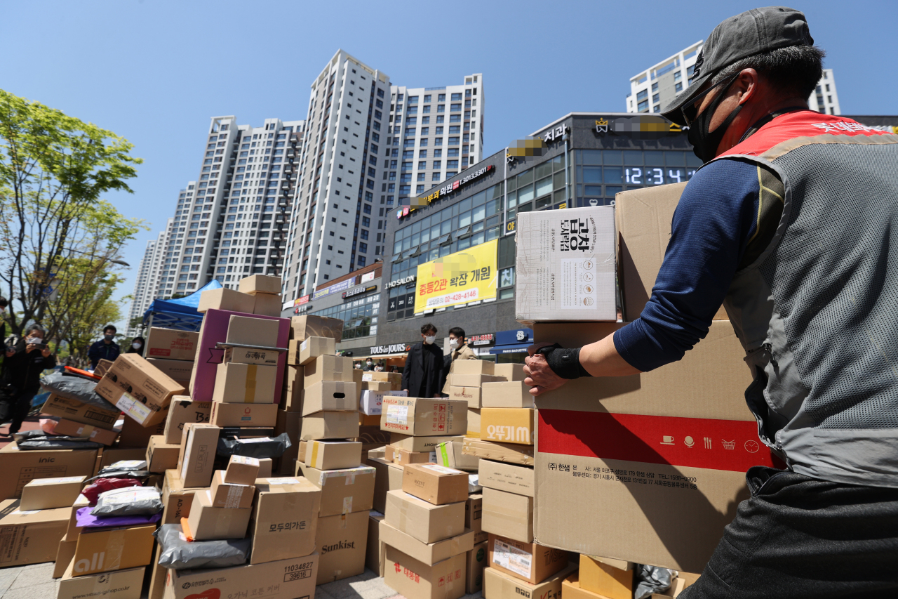 A delivery worker places parcels by the entrance to an apartment complex with 5,000 households in Gangdong-gu, eastern Seoul, on April 15. (Yonhap)