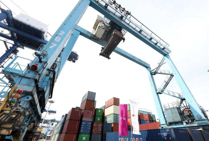 A shipyard crane, able to send camera feeds from its sensors and cameras to a control room via 5G network, picks up a cargo container at a container terminal in Busan Port. (LG U+)