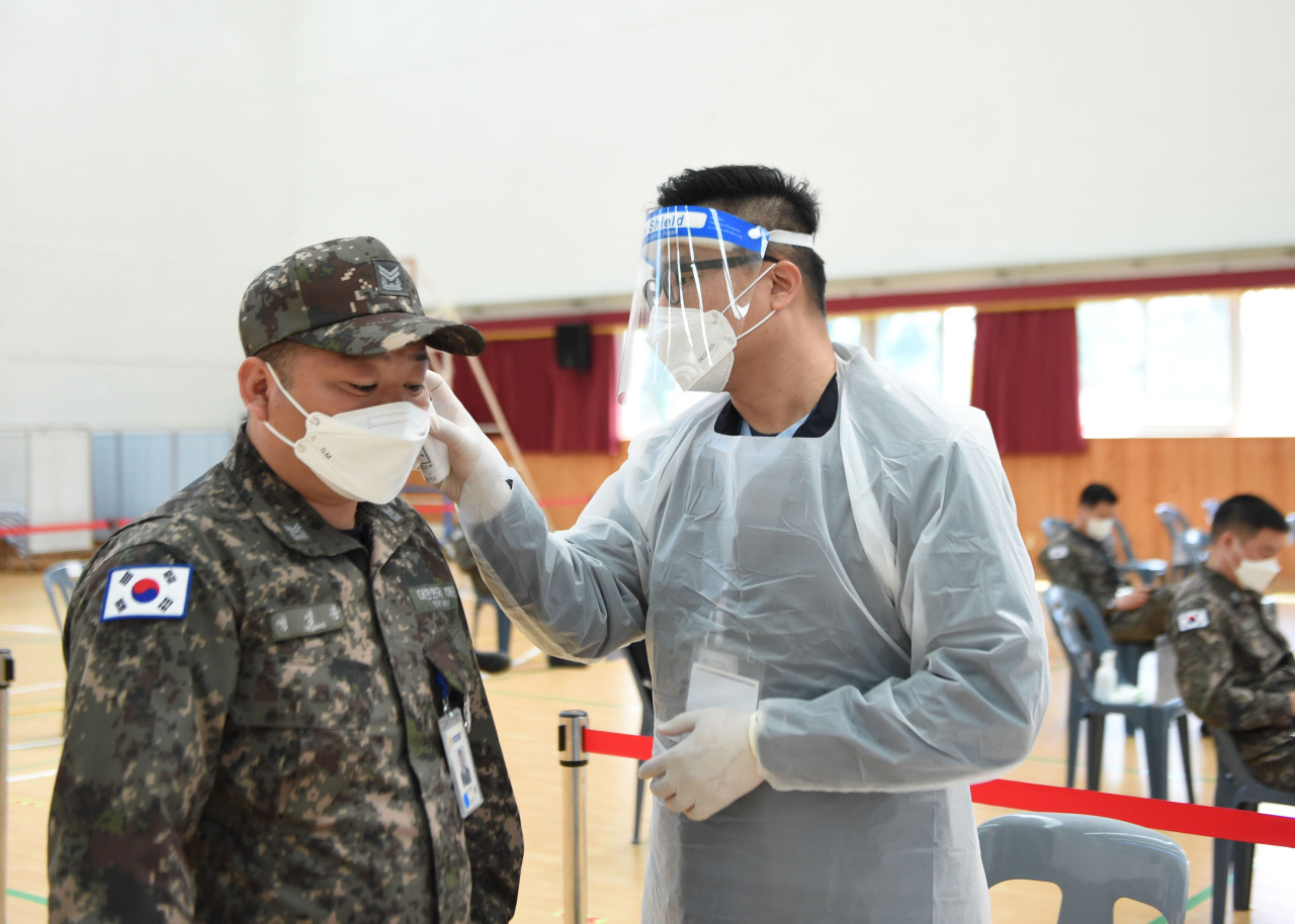 A service member of the Navy Submarine Command undergoes a temperature check prior to receiving a COVID-19 shot at a makeshift center in the southeastern city of Changwon, North Gyeongsang Province, last Wednesday, in this photo provided by the defense ministry. (Ministry of National Defense)