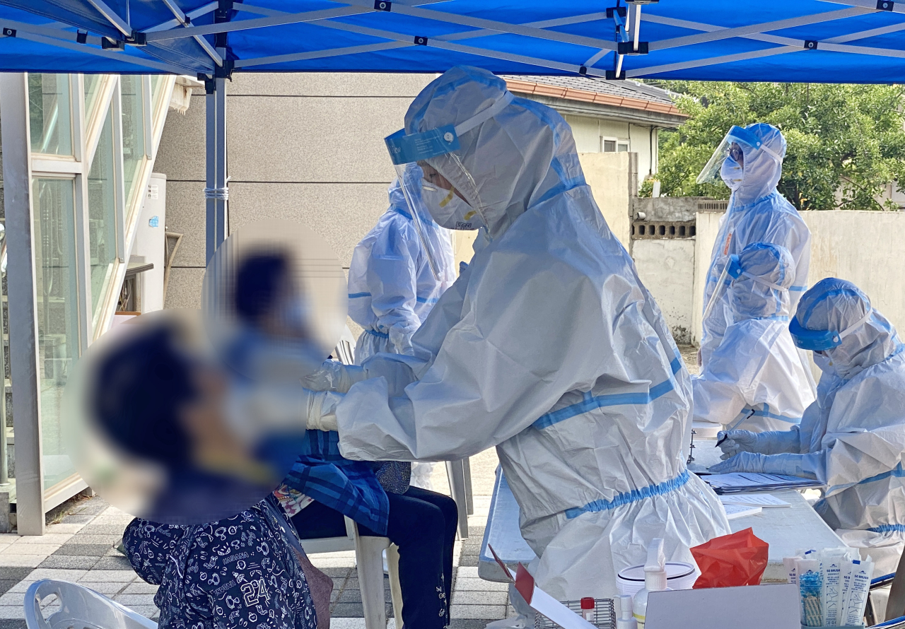 Residents in the city of Gyeongju, 371 kilometers southeast of Seoul, where community infections took place, take new coronavirus tests in front of a village hall on Sunday. (Yonhap)