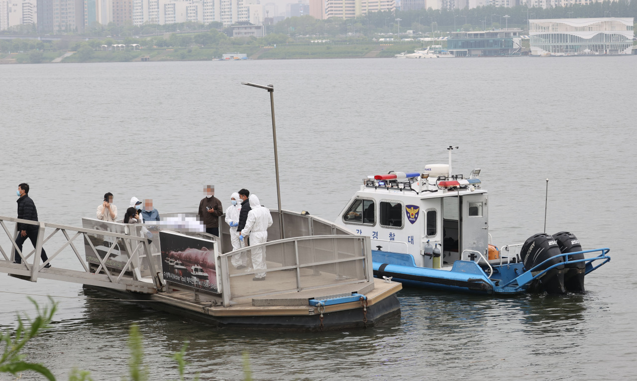 Members of a police team stand over the body of a student they found dead in the Han River on April 30. He had been missing for six days. (Yonhap)