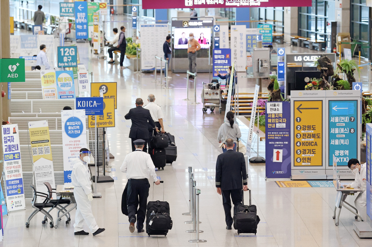 In this file photo taken on April 21, 2021, health workers guide arrivals at Incheon International Airport, west of Seoul. (Yonhap)