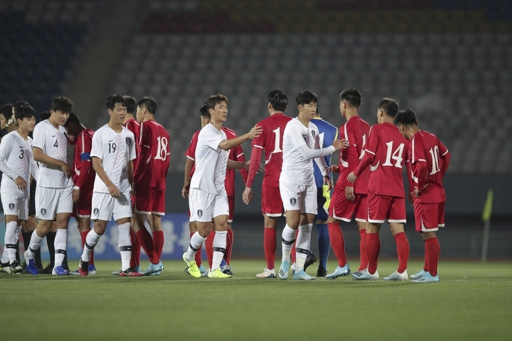 In this photo provided by the Korea Football Association, players from South Korea (in white) and North Korea (in red) acknowledge each other after playing to a scoreless draw in a World Cup qualifying match at Kim Il-sung Stadium in Pyongyang on Oct. 15, 2019. (Korea Football Association)