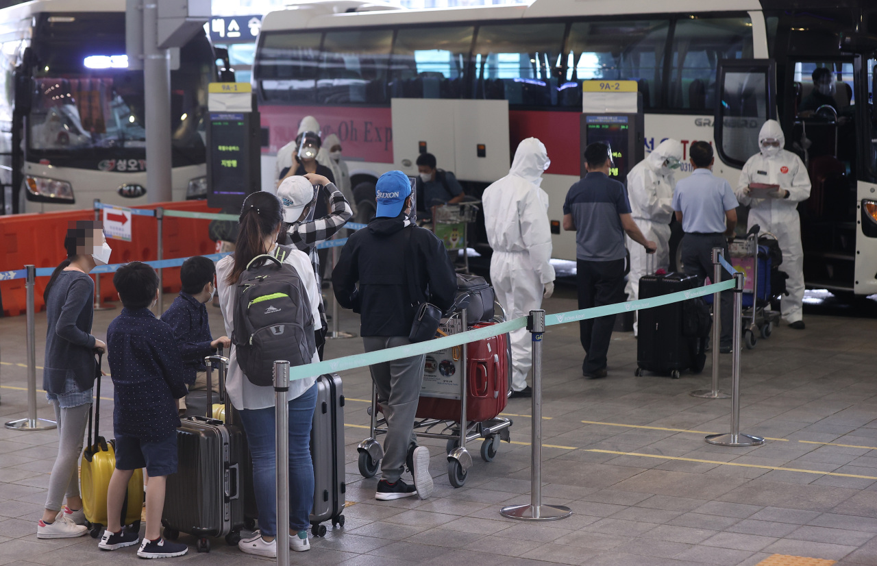 South Korean residents wait to board buses at Incheon airport, west of Seoul, on Tuesday, to head for quarantine facilities after arriving from virus-hit India via a special flight operated by Indian air carrier Vistara. (Yonhap)
