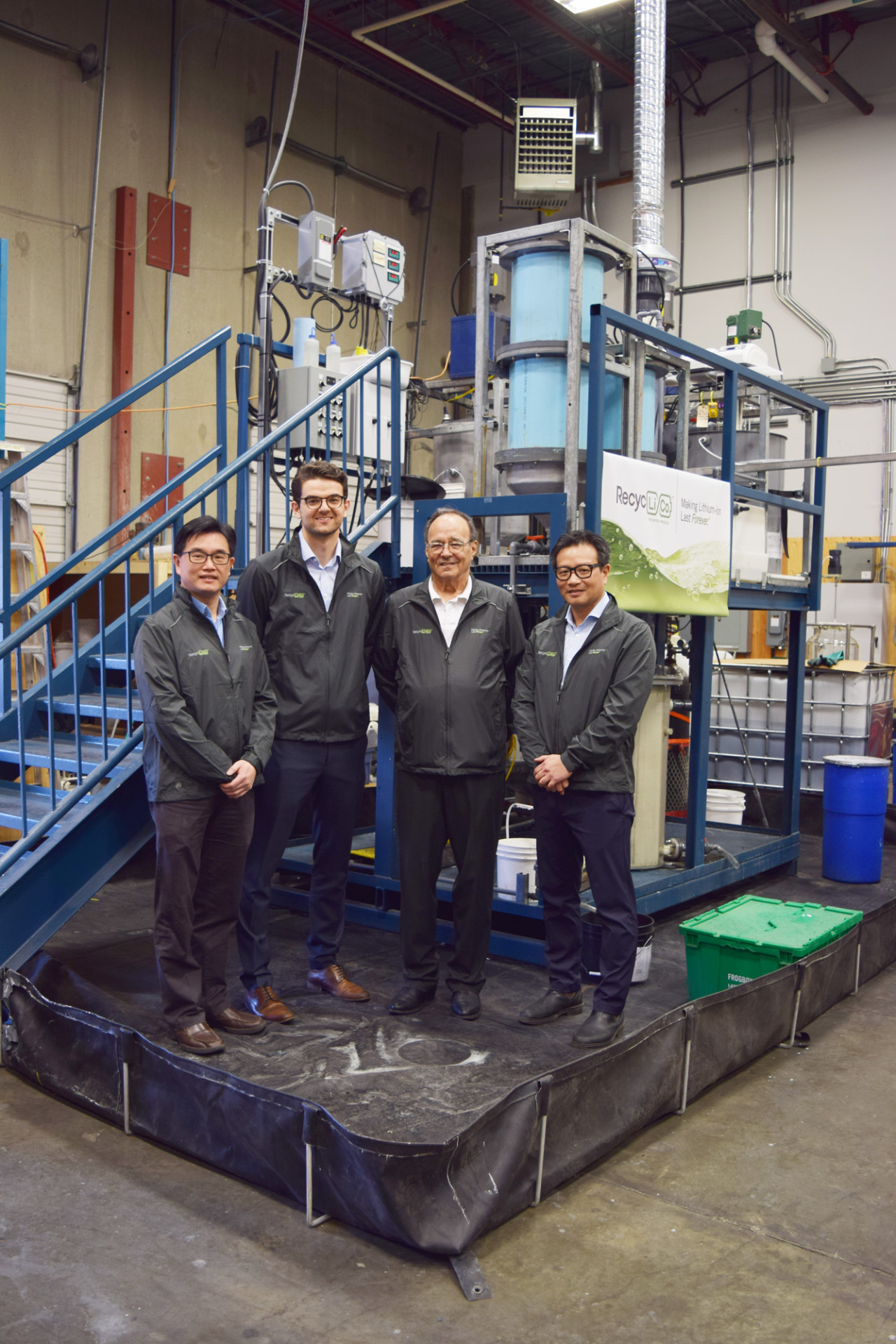 Cap/ American Manganese CEO Larry Reaugh (second from right) and chief technology officer Zarko Meseldzija (third from right) pose for a photo in front of the company's battery recycling system. (American Manganese)
