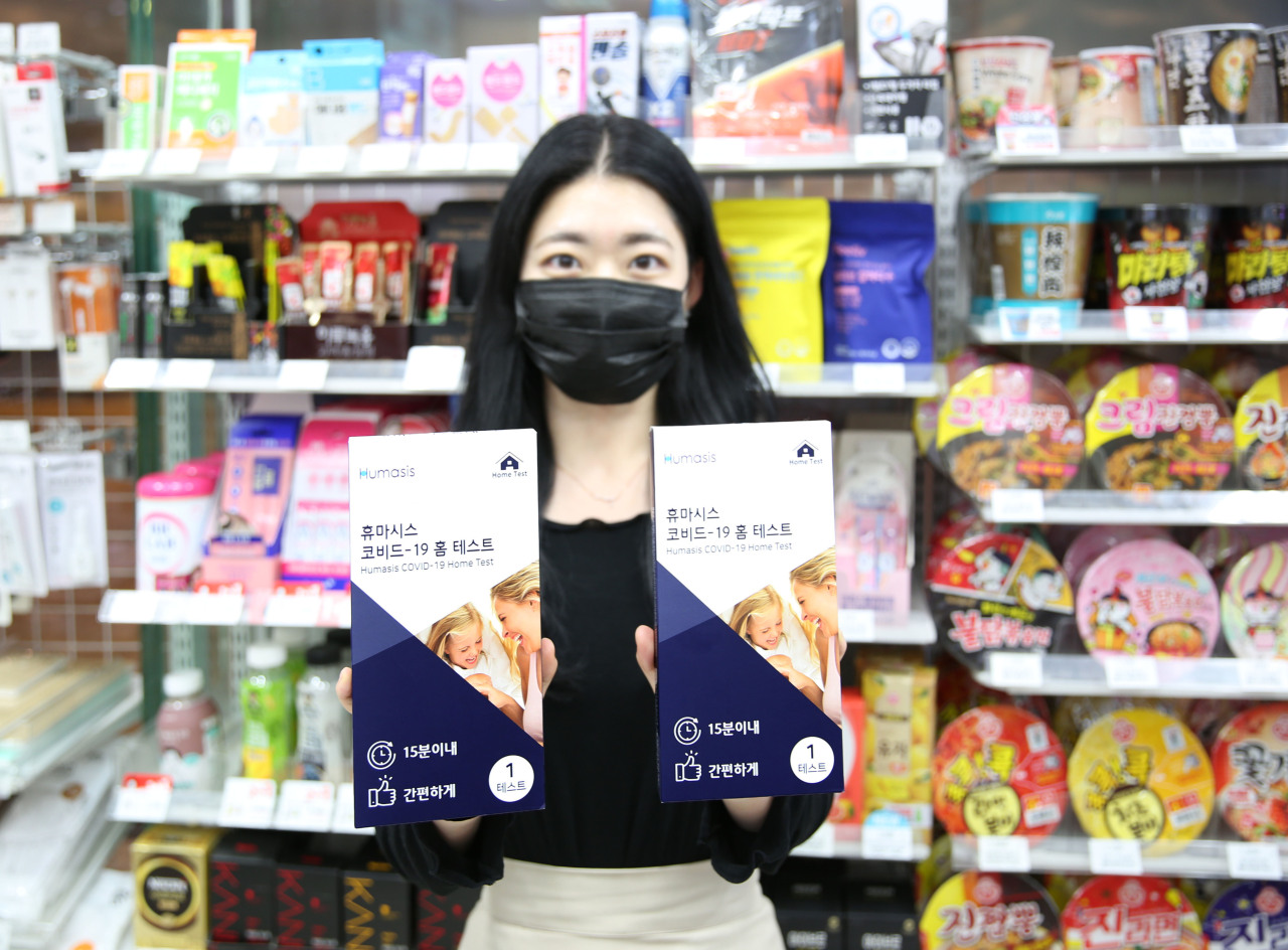 A model holds COVID-19 test kits developed by Humasis at a branch of convenience store chain GS25. (GS25)