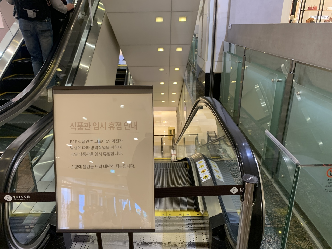 A notice for the temporary closure of a department's supermarket in downtown Seoul due to COVID-19 informs people next to an escalator leading to the store on Wednesday. (Yonhap)