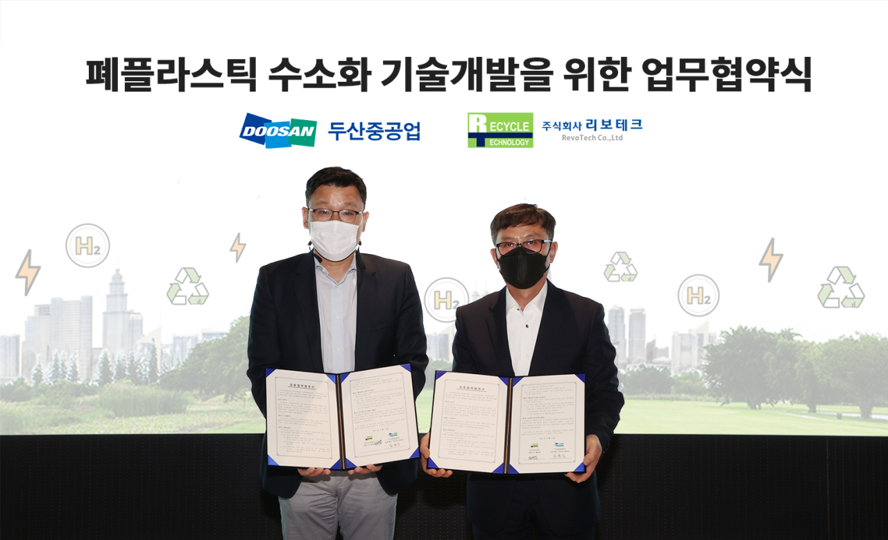 Doosan Heavy Industries & Construction Vice President Song Yong-jin (left) and RevoTech CEO Hwang Byung-jik pose for a photo after signing an agreement to extract hydrogen from plastic waste at Bundang Doosan Tower on Thursday. (Doosan Heavy Industries & Construction)