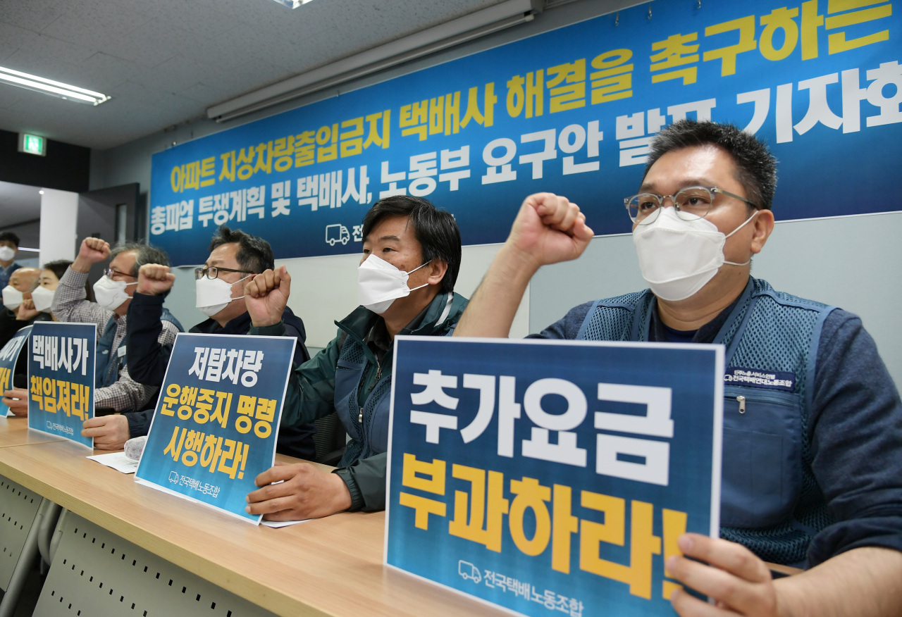 Unionized delivery workers chant slogans during a press conference Friday held to announce that the union has voted to launch a strike over an ongoing conflict with an apartment complex and its residents over a ban on ground-floor parking. (Yonhap)