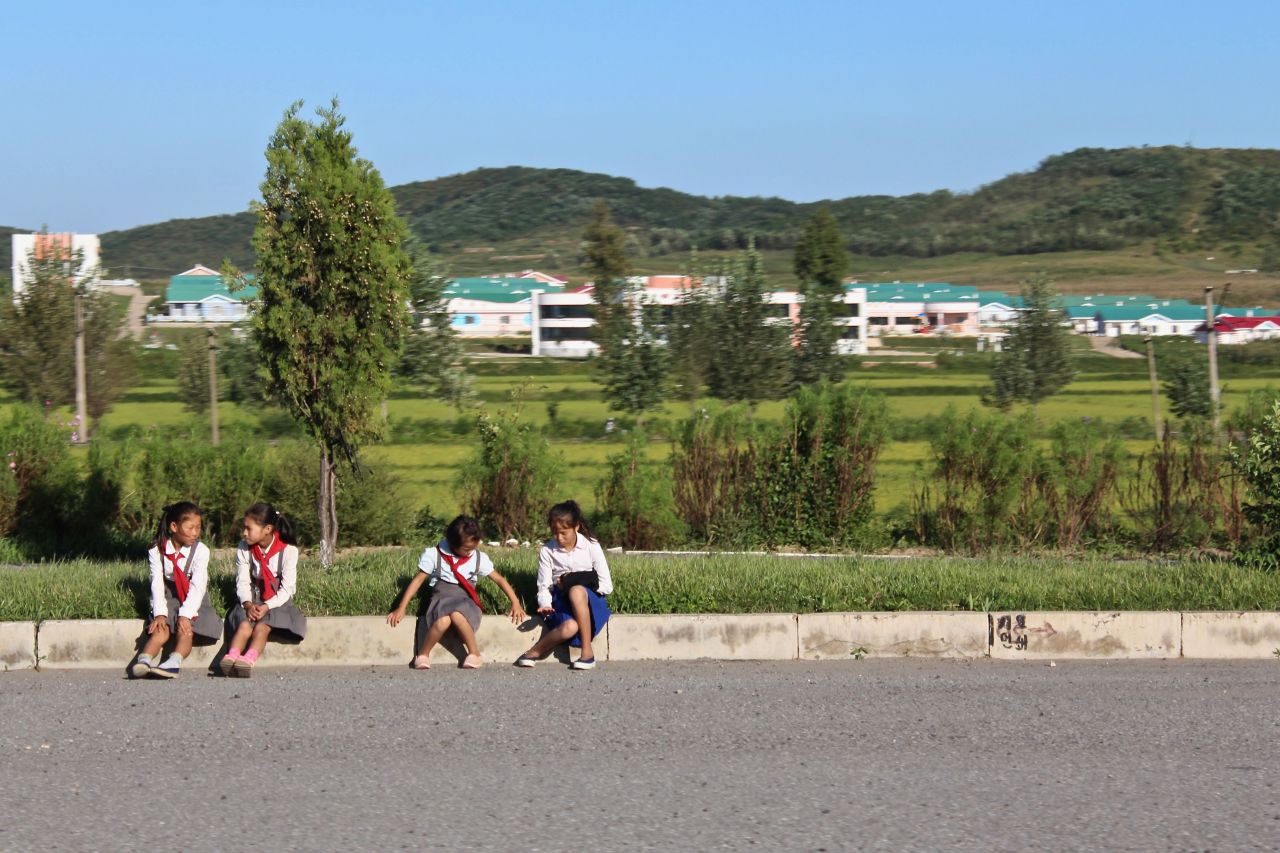 A group of children sit by the roadside on Youth Hero Highway in September 2018. (Lindsey Miller)