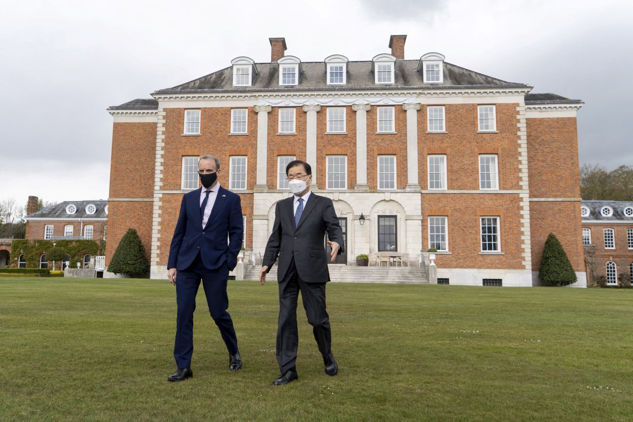 Britain's Foreign Secretary Dominic Raab, left, and South Korea's Minister of Foreign Affairs, Chung Eui-yong, walk in the grounds of Chevening House, Kent, England on Thursday. (AP-Yonhap)