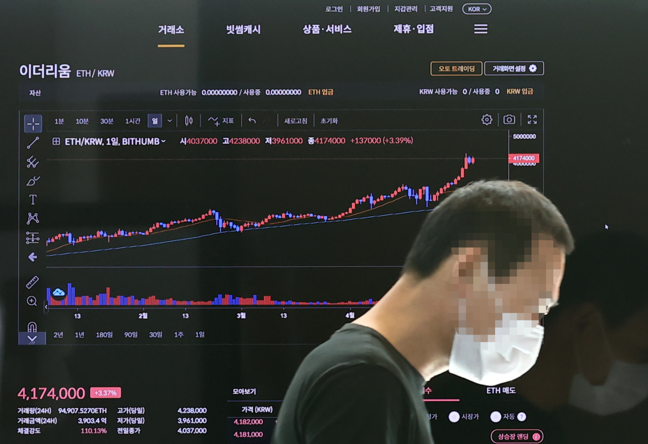 A man walks past a digital board showing the ethereum price at Bithumb on Friday. (Yonhap)
