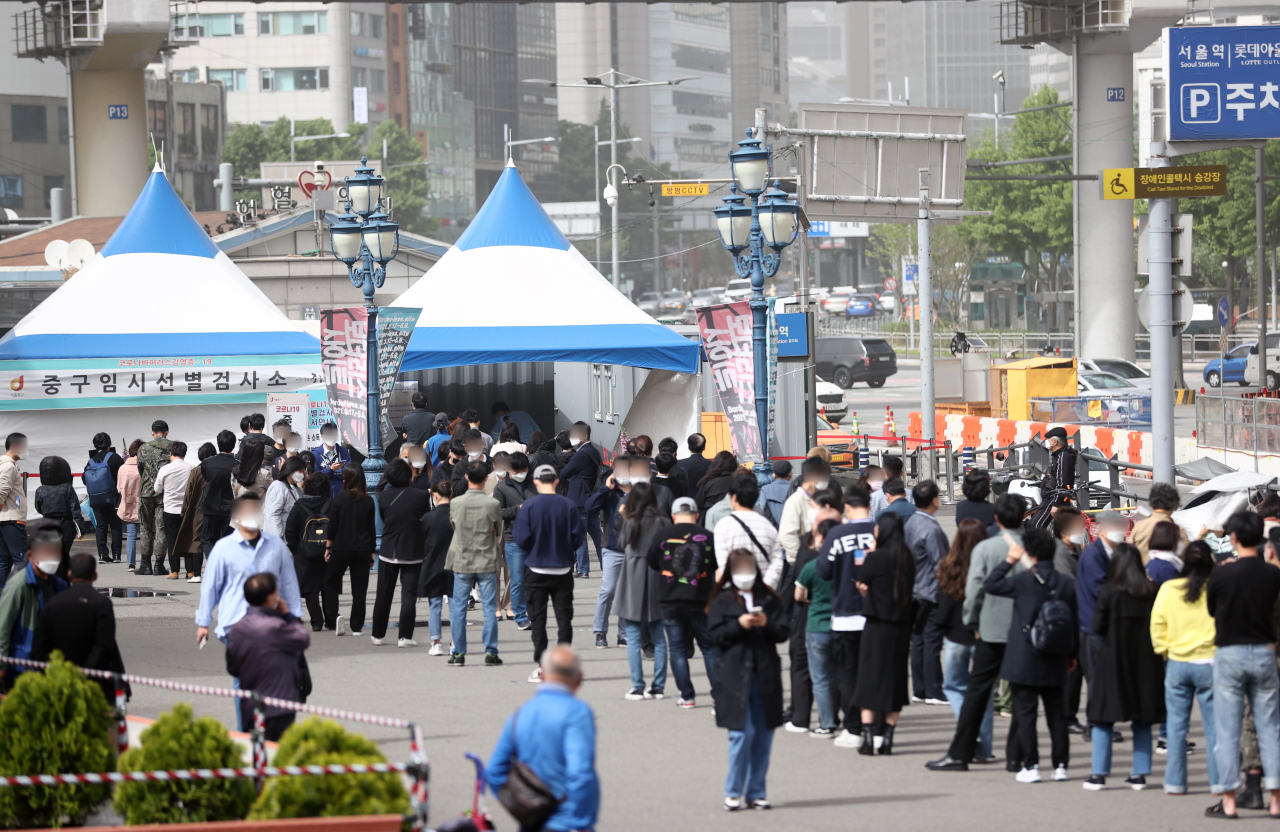 Citizens wait in a long line to receive virus tests at a makeshift COVID-19 testing clinic in Seoul on Friday. (Yonhap)