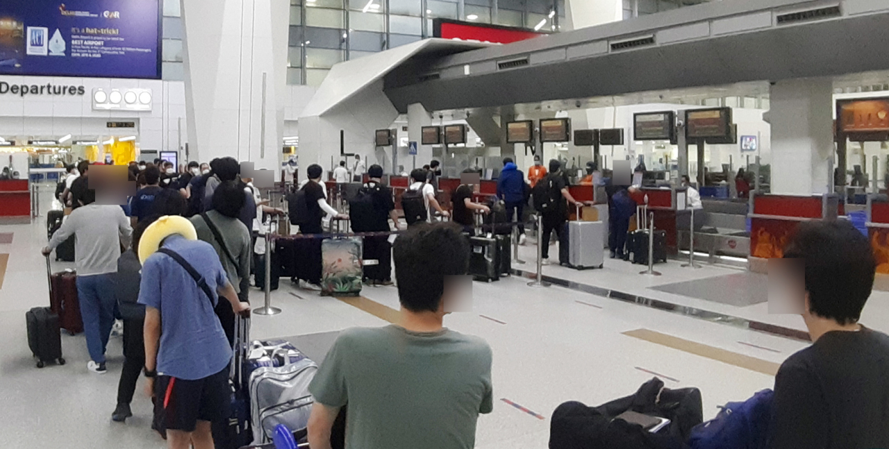 This photo, provided by the South Korean Embassy in New Delhi, shows South Korean nationals checking in to board a special flight to South Korea at Indira Gandhi International Airport in Delhi, India, on Saturday. (South Korean Embassy)