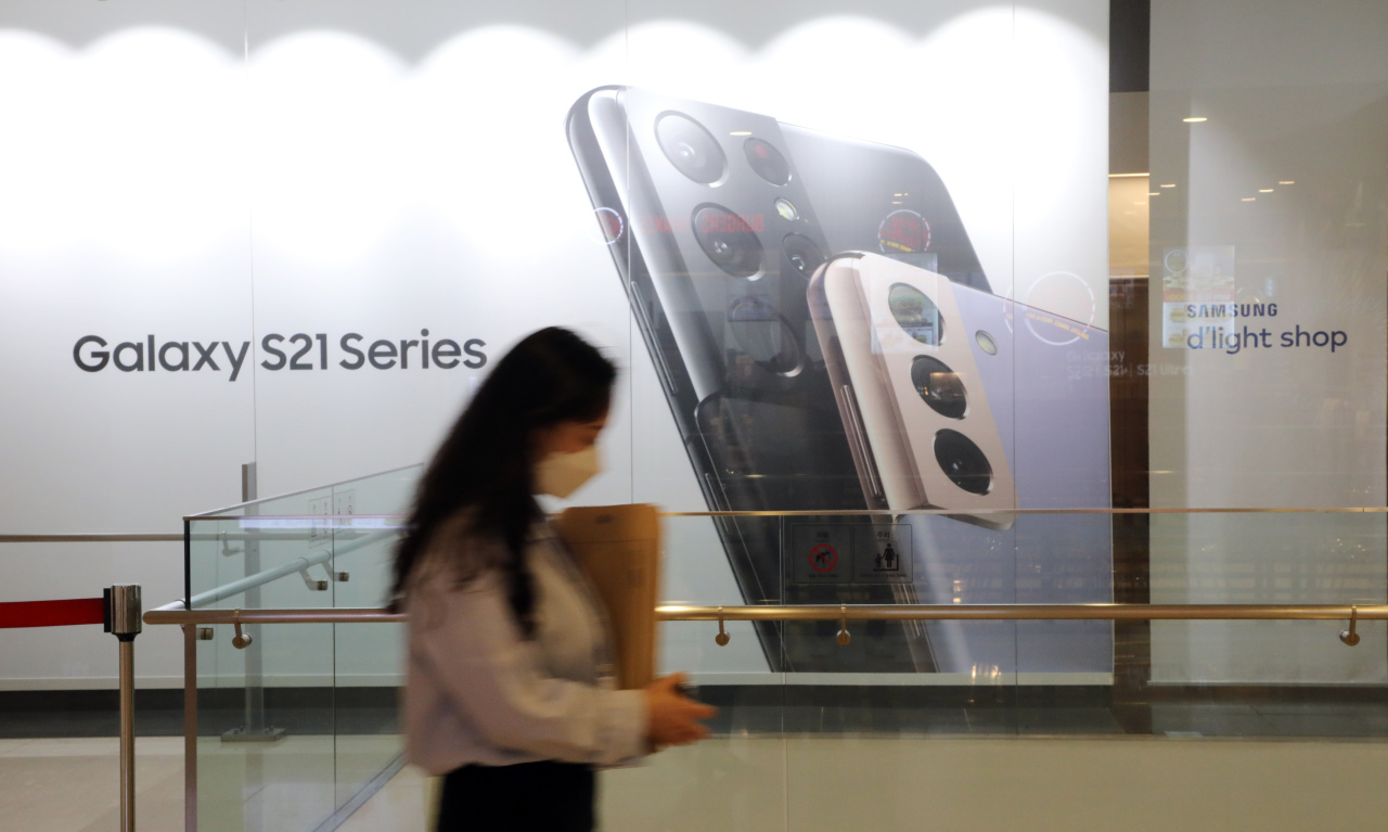 A person walks by an advertisement board for Samsung Electronics Co.'s Galaxy S21 series smartphones on April 29, 2021, at the company's building in southern Seoul. (Yonhap)