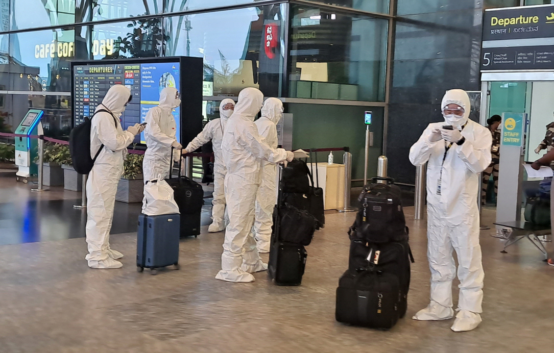 Air cabin crew members on chartered flight carrying South Korean citizens from virus-hit India are dressed in hazmat suits. (Yonhap)