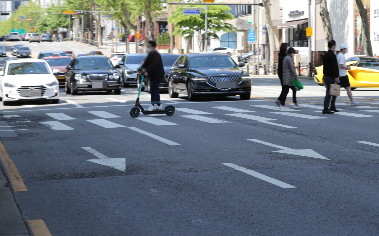 An electric scooter user crosses a street in Seoul earlier this month. Starting Thursday, all electric scooter users in South Korea will be required to have driver's licenses and wear protective helmets. (Yonhap)