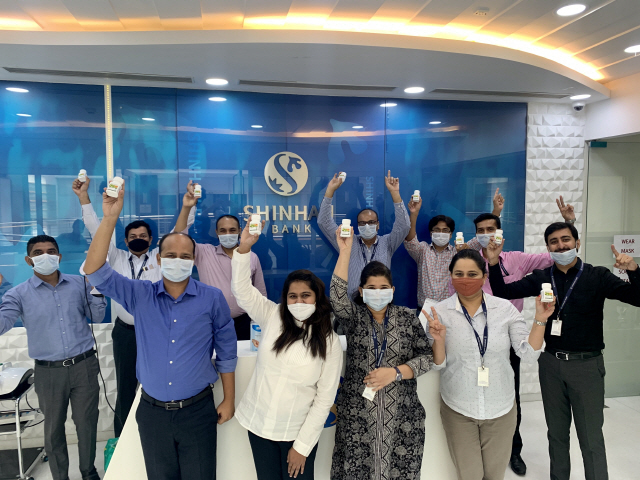 Employees at one of Shinhan Bank's branch in India hold up gifts from Korea sent by CEO Jin Ok-dong in August 2020. (Shinhan Bank)
