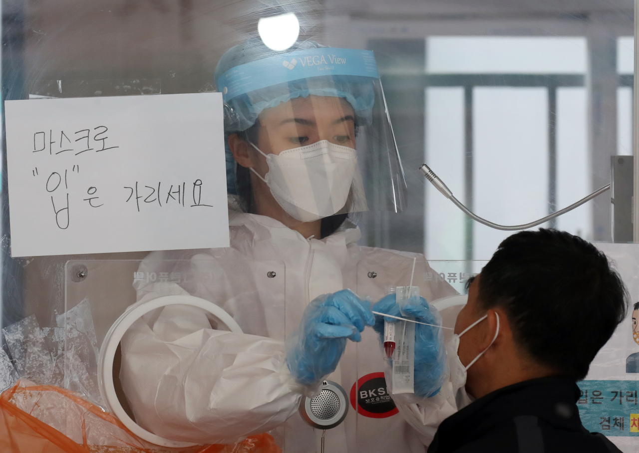 A medical worker collects a sample from a man to test for COVID-19 at a makeshift virus testing center near Seoul Station in Seoul on Monday. (Yonhap)