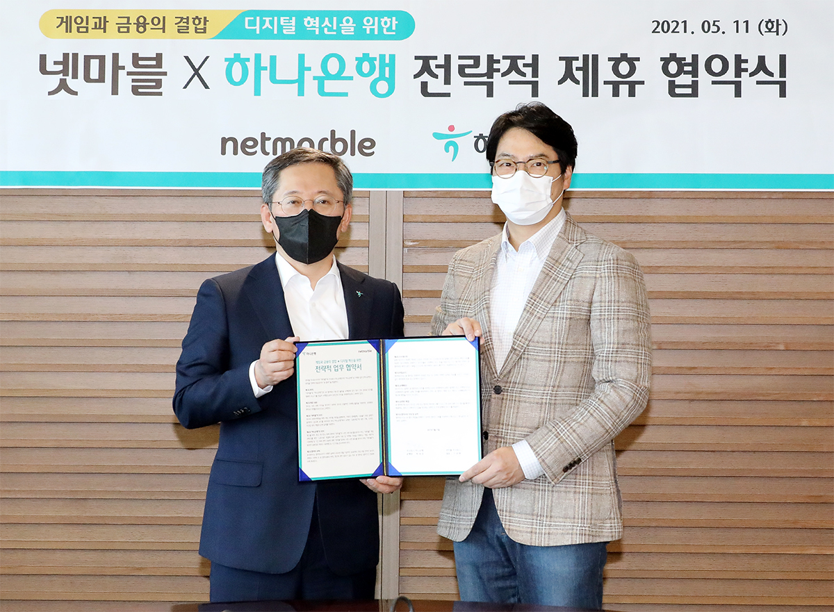 Cap-Hana Bank President Park Sung-ho and Netmarble co-CEO Lee Seung-won pose for a photo after signing a business agreement to jointly develop innovative digital financial services at the bank's headquarters in Seoul, Tuesday. (Yonhap)