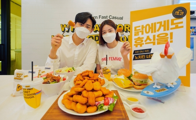 """No Brand Burger staff pose with No Chicken Nugget, next to a sign reading, """"Give chickens a rest."""" (Shinsegae Foods)"""