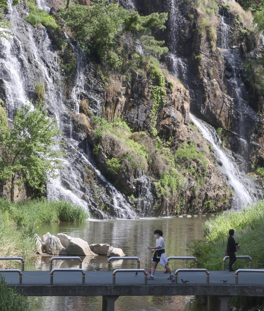 People walk past an artificial waterfall in western Seoul on Wednesday, amid early summer-like weather. (Yonhap)