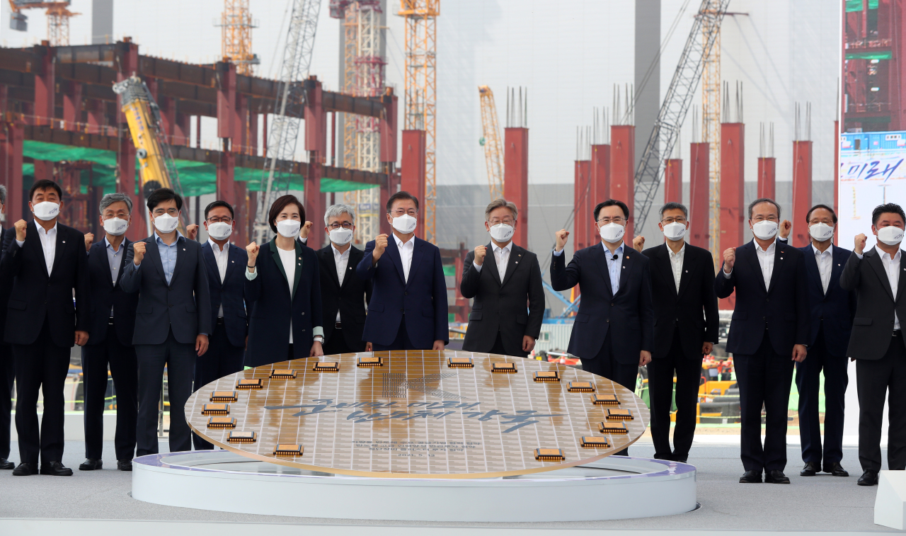 President Moon and government officials pose at a construction site for Samsung's third chip manufacturing plant in Pyeongtaek, Gyeonggi Province, on Thursday. (Yonhap)