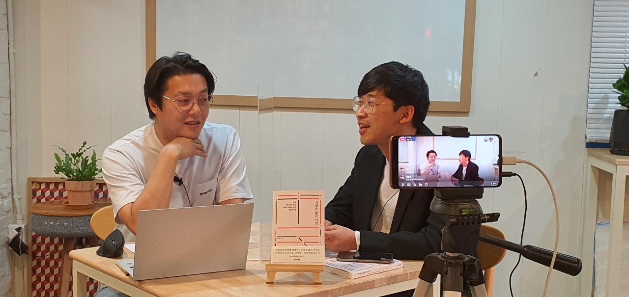 "Cho Seong-ju (left), head of Powerplant, and Kang Nam-kyu (right), author ofthe book ""The Civilians not yet Present."" (Kim Hae-yeon/ The Korea Herald)"