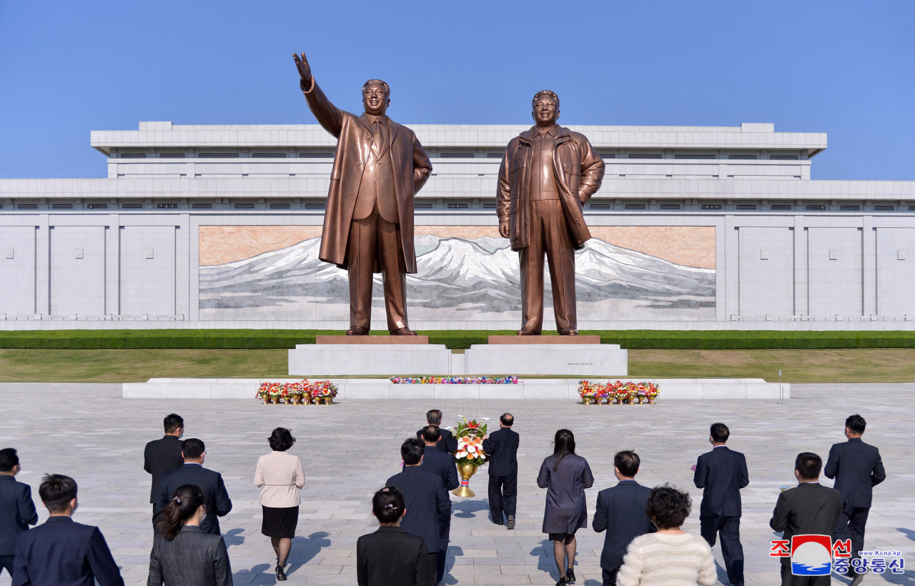 This photo, released by the Korean Central News Agency, shows North Korean people offering flowers in front of the statues of late North Korea founder Kim Il-sung and his late son Kim Jong-il in Pyongyang on the occasion of the 89th founding anniversary of the Korean People's Revolutionary Army on April 25. (Yonhap)