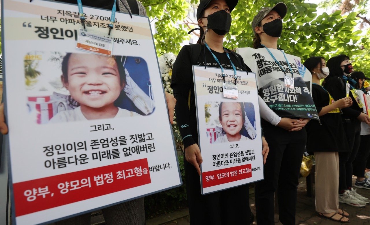 Demonstrators hold signs in front of the Seoul Southern District Court demanding strong punishment for the adoptive parents accused of abusing their daughter on Friday. (Yonhap)