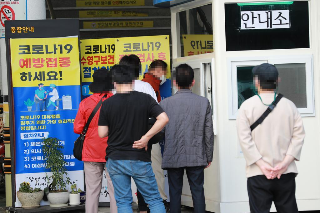 This photo taken on Friday, shows people lining up to take a coronavirus test at a public health center in Busan, 453 kilometers southeast of Seoul. (Yonhap)