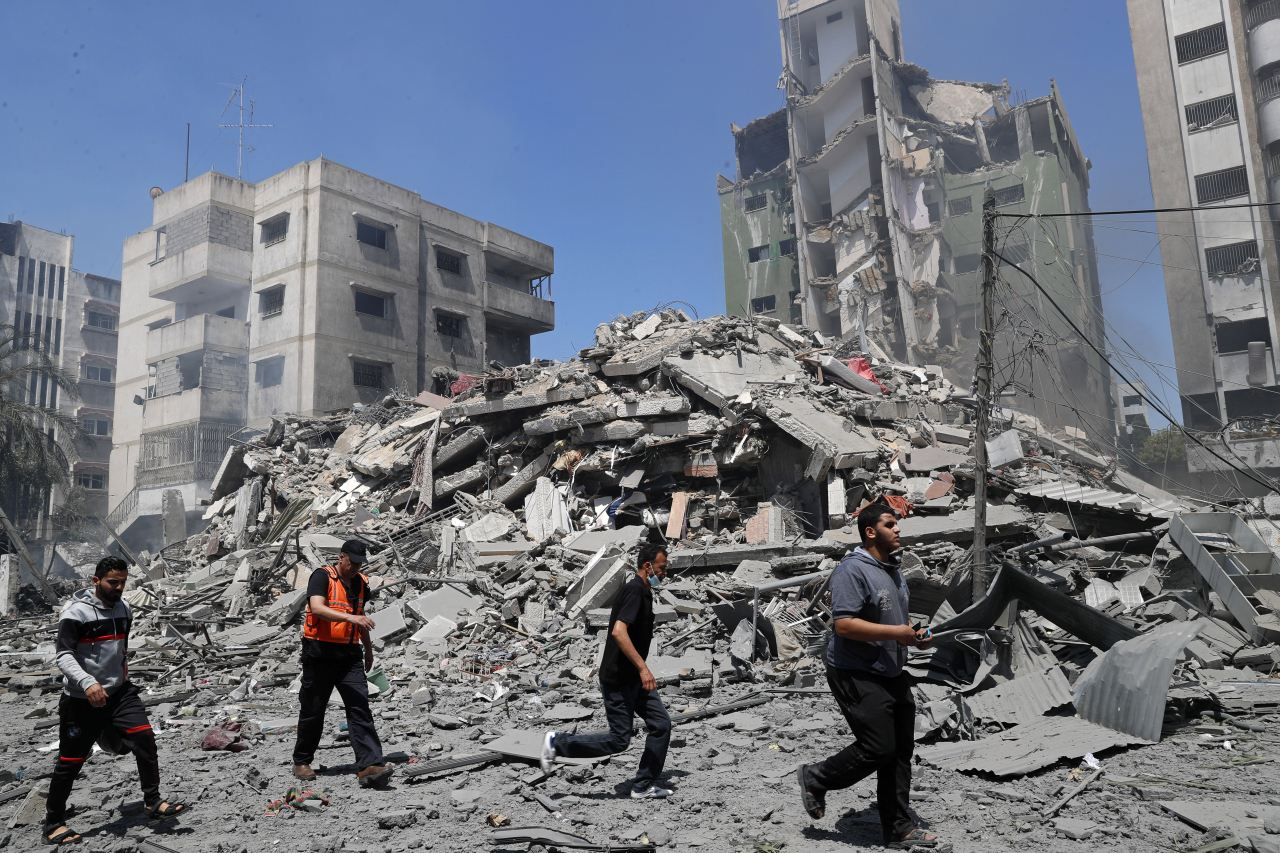 People inspect the the rubble of the Yazegi residential building that was destroyed by an Israeli airstrike, in Gaza City, Sunday. (AP)
