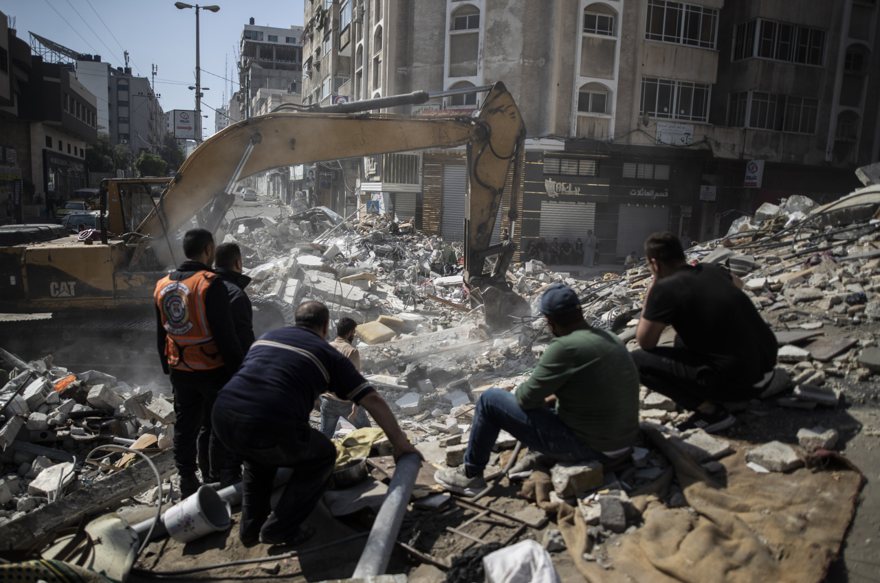 Palestinian rescuers search for survivors under the rubble of destroyed residential buildings following deadly Israeli airstrikes in Gaza City, Sunday. (AP)