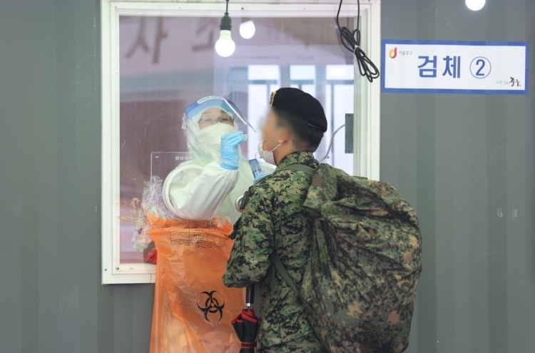 In this file photo taken on March 12, 2021, a service member receives a coronavirus test at a makeshift clinic set up near Seoul Station. (Yonhap)