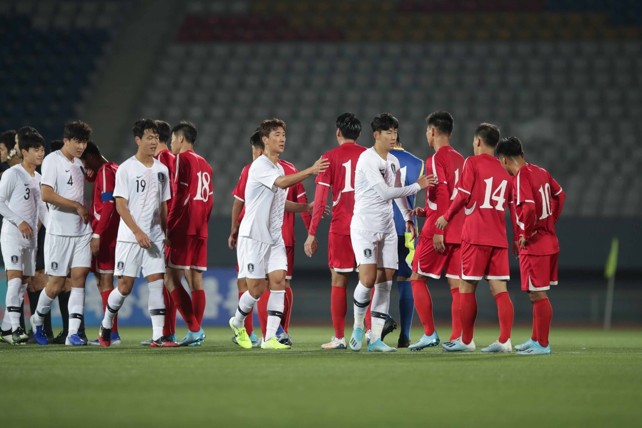 In this file photo provided by the Korea Football Association, players from South Korea (in white) and North Korea (in red) acknowledge one another after playing to a scoreless draw in a World Cup qualifying match at Kim Il-sung Stadium in Pyongyang on Oct. 15, 2019. (Korea Football Association)