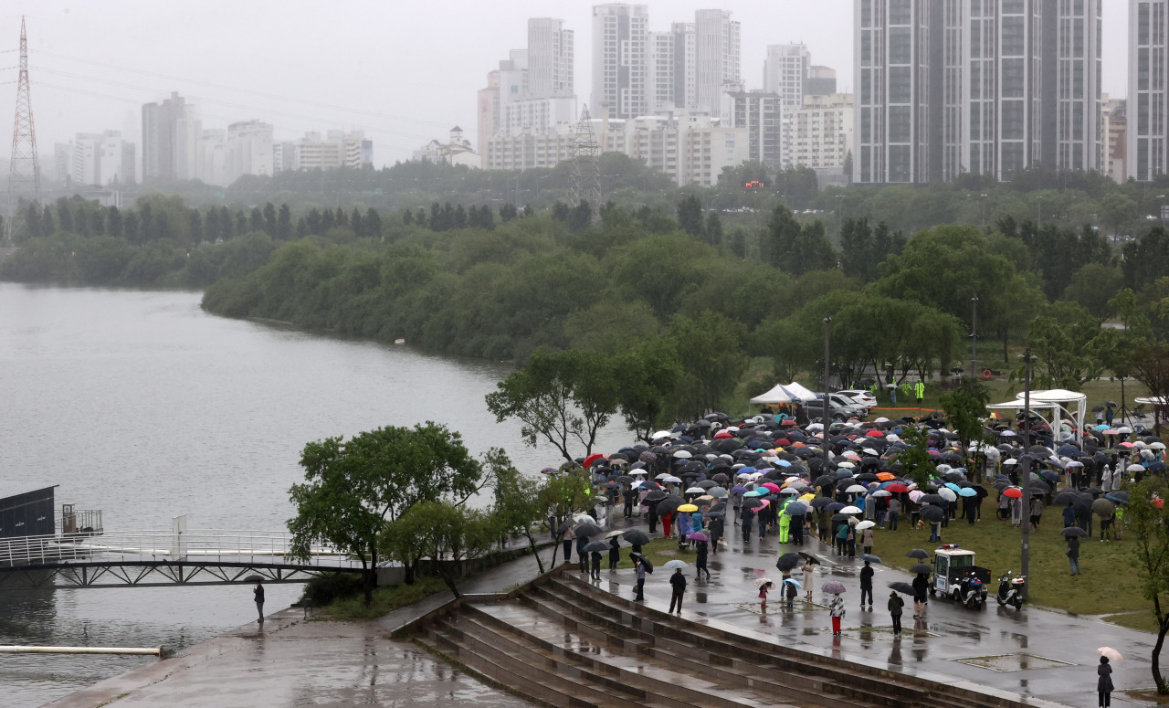 People hold a rally for the late Sohn Jung-min at a park along the Han River in Seoul on Sunday. (Yonhap)