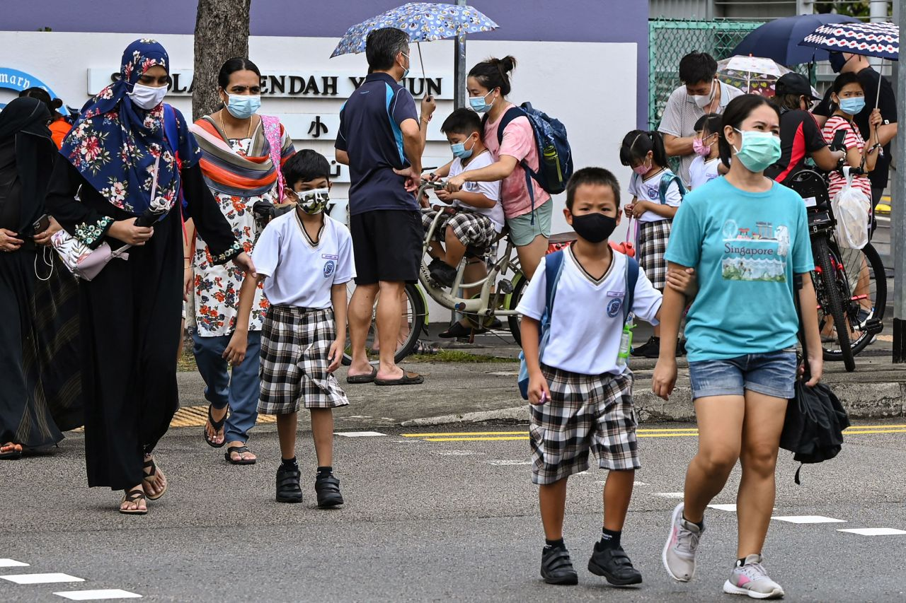 Children walk home with their guardians after school in Singapore on Monday, as the country prepares to shut all schools and switch to home-based learning until the end of the term due to a rise in the number of COVID-19 coronavirus cases. (Yonhap)