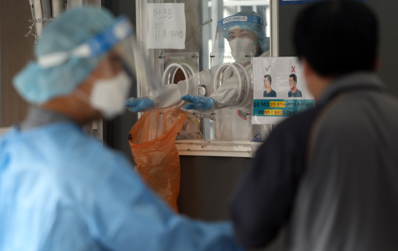 Medical workers carry out tests at a coronavirus testing center in Seoul on Tuesday. (Yonhap)