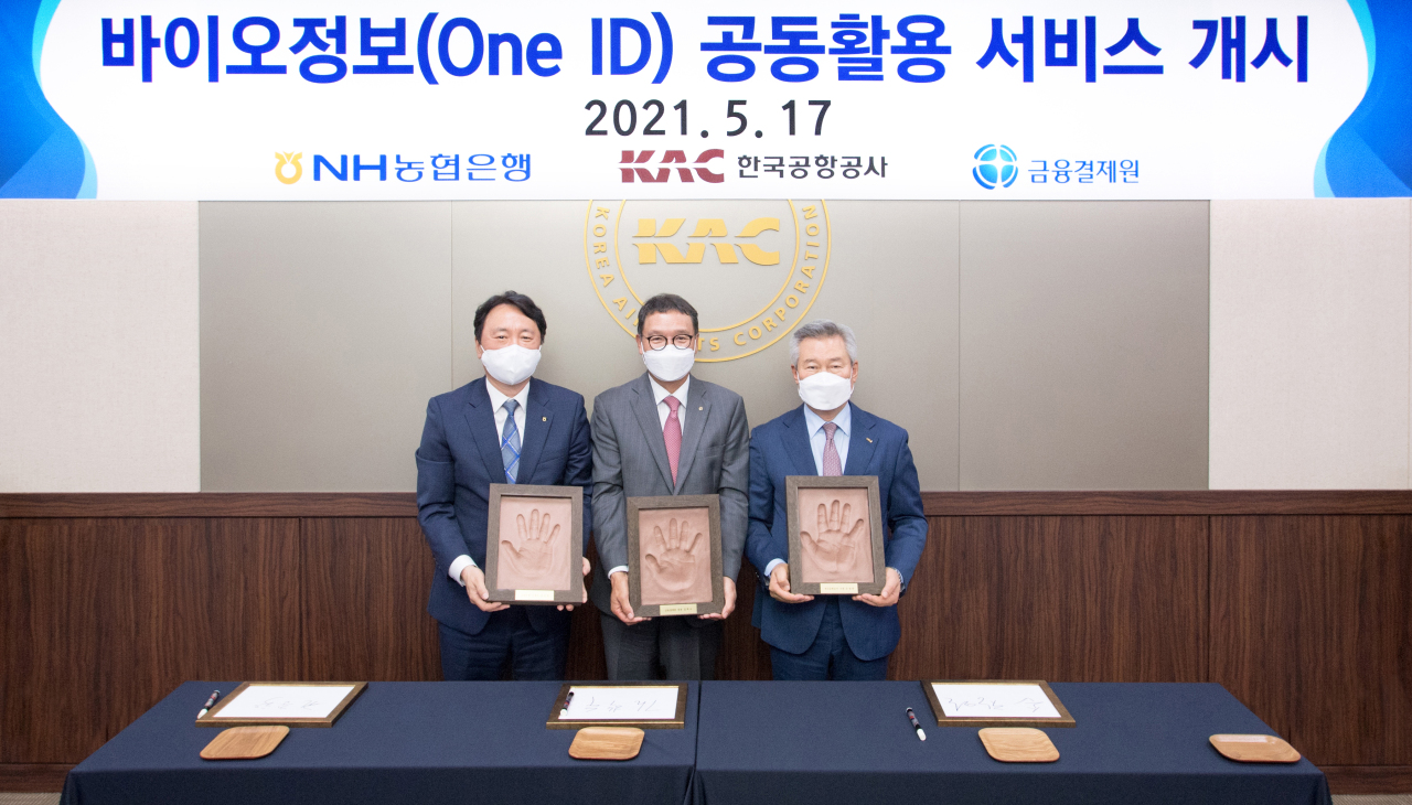 NH NongHyup Bank CEO Kwon Joon-hak (first from left), Kim Hak-soo, president of the Korea Financial Telecommunications and Clearings Institute (center) and Korea Airports Corp. President and CEO Son Chang-wan hold up their hand prints during an event celebrating the launch of a joint bioinformation service at Gimpo International Airport, Monday. (NH NongHyup Bank)