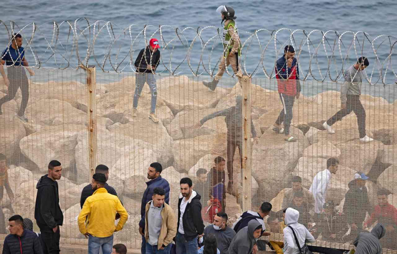 Moroccan migrants slip through a fence in the northern town of Fnideq in an attempt to cross the border from Morocco to Spain`s North African enclave of Ceuta, Tuesday. (AFP-Yonhap)
