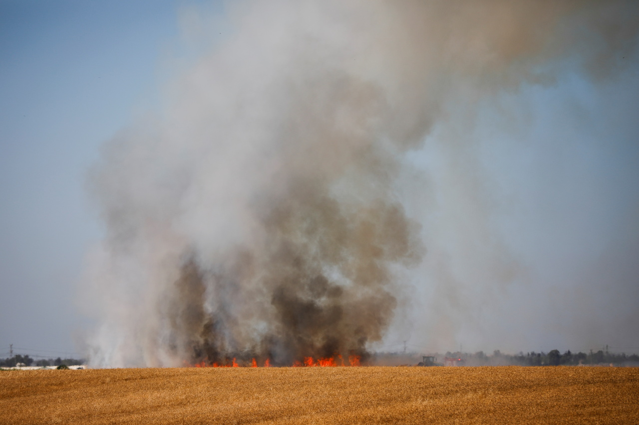 A fire burns on a field following rockets that were fired from the Gaza Strip to Israel, near Kiryat Gat, southern Israel, Tuesday. (Reuters-Yonhap)