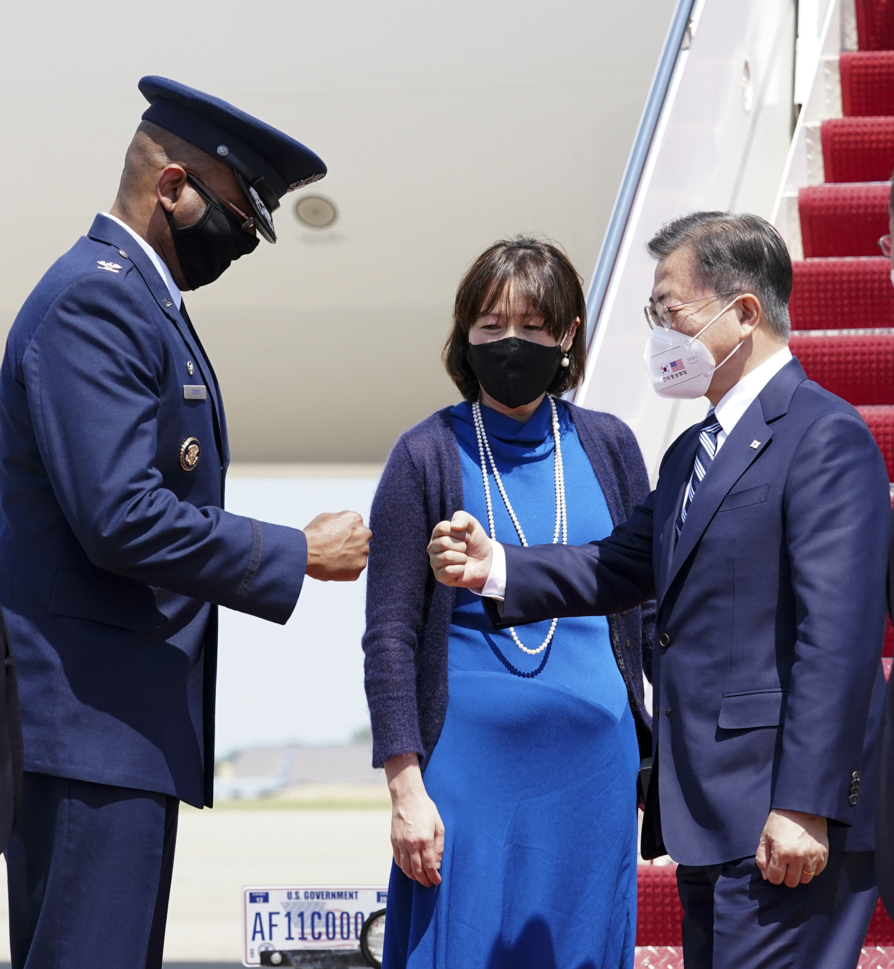 South Korean President Moon Jae-in (R) bumps fists with a US military official upon arriving at Andrews Air Force Base in Maryland on Wednesday. (Yonhap)