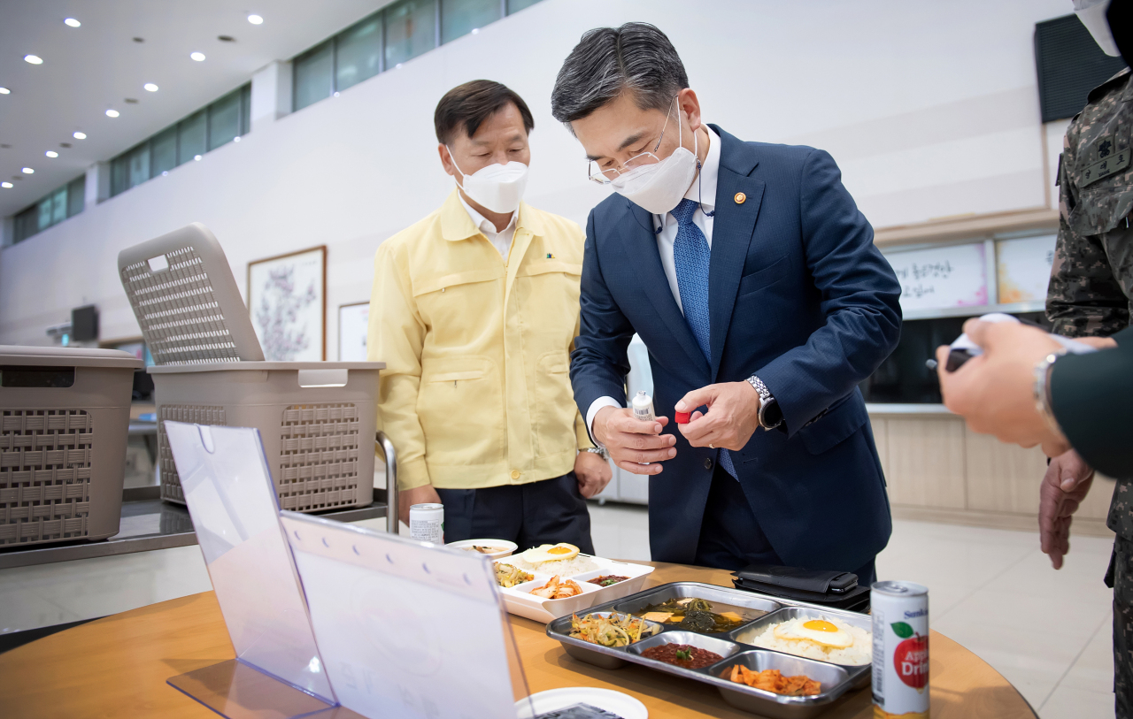 Defense Minister Suh Wook (C) inspects meals for service members at a unit in Seoul on Friday, in this photo provided by his office. (Ministry of National Defense)