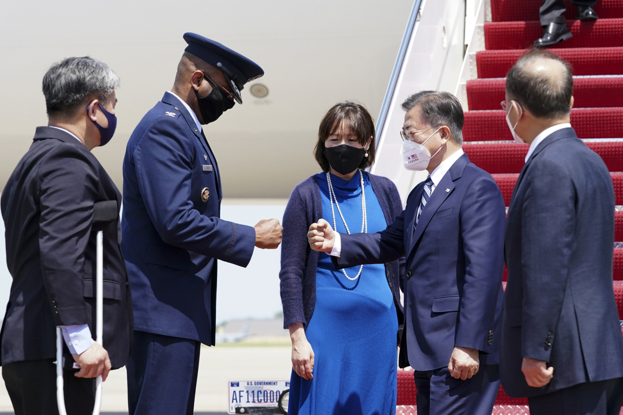 South Korean President Moon Jae-in (second from right) bumps fists with a US military official after arriving at the Joint Base Andrews near Washington on Wednesday. (Yonhap)