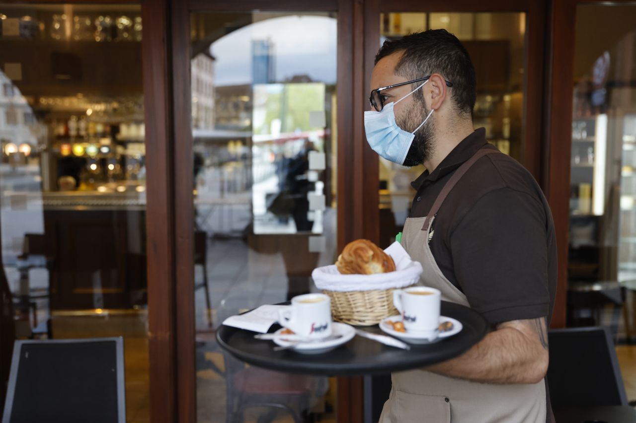 A waiter carries cups of coffee on a tray in a cafe in Eastern France. (Yonhap)