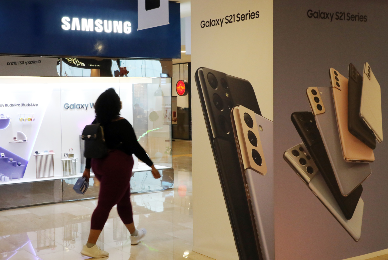 A person is seen walking past Samsung D'light store, which displays a promotional image of Samsung Electronics flagship smartphone Galaxy S21, in Seocho-gu district, Seoul in April. (Yonhap)