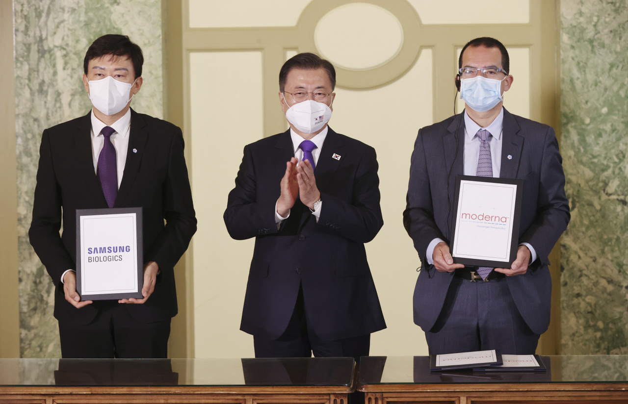 President Moon Jae-in (center) poses for a photo with John Rim (left), CEO of Samsung Biologics, and Stephane Bancel, CEO of Moderna, at a hotel in Washington on Saturday. (Yonhap)