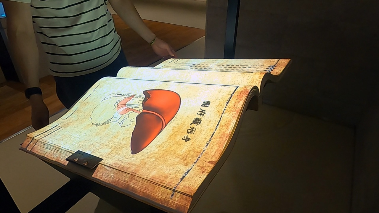 """A visitor looks at a digital book that presents Heo Jun's """"Dongui Bogam,"""" from the Joseon Dynasty. (Kim Hae-yeon/ The Korea Herald)"""