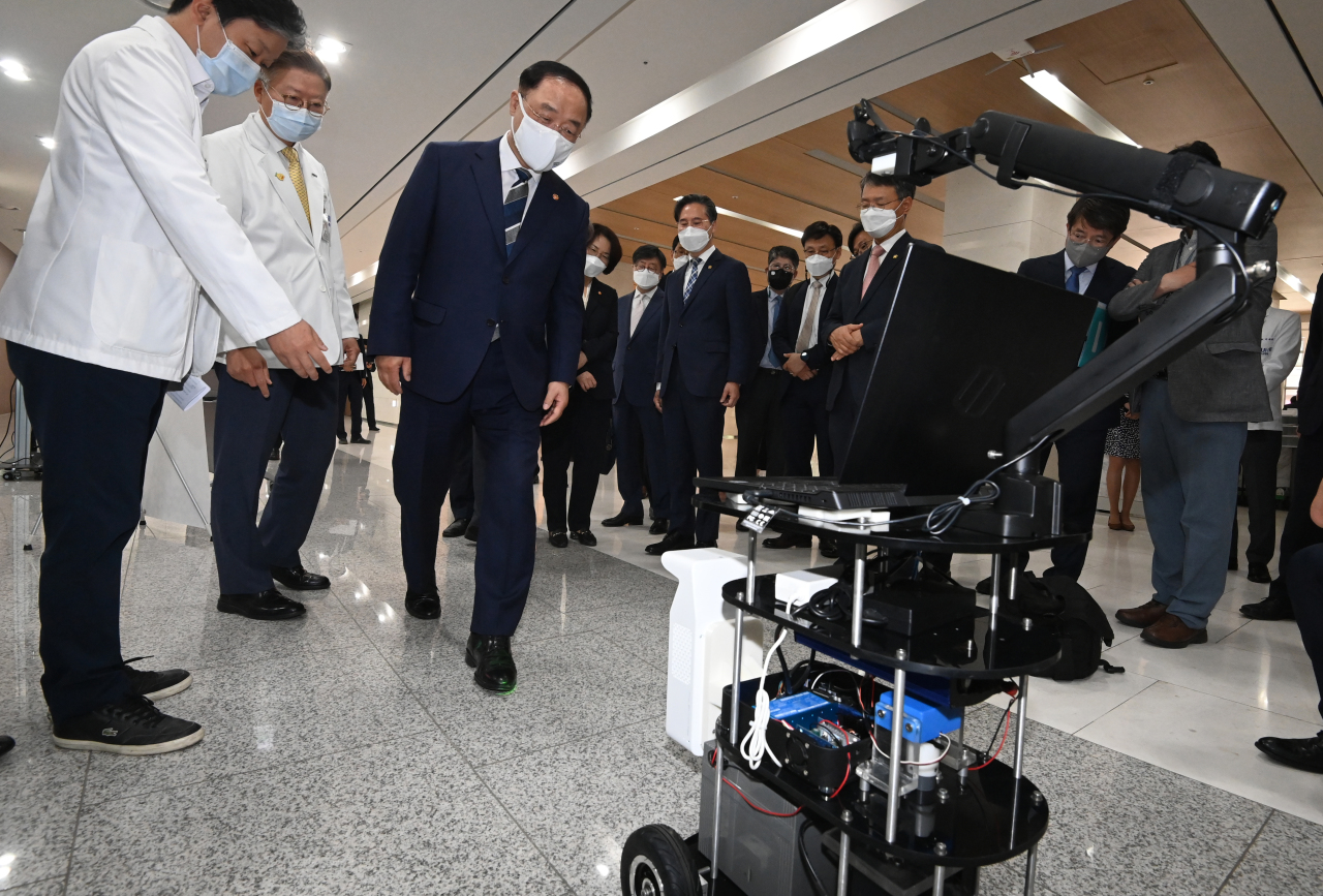 Finance Minister Hong Nam-ki looks at a walking assist robot for Parkinson's disease patients at Seoul National University's Medical Research Center for Innovation in Seoul, Wednesday. (Yonhap)
